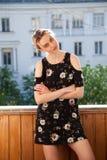 Blondes Mädchen in einem Kleid mit Blumen auf dem Hintergrund des Hauses Stockfoto