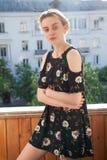 Blondes Mädchen in einem Kleid mit Blumen auf dem Hintergrund des Hauses Lizenzfreies Stockfoto