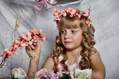 Blondes Mädchen in einem rosa Kleid mit Blumen Lizenzfreies Stockfoto
