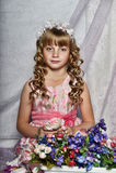 Blondes Mädchen in einem rosa Kleid mit Blumen Lizenzfreie Stockfotografie