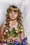 Blondes Mädchen in einem rosa Kleid mit Blumen Stockfotos