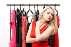 Blondes Mädchen in einem roten Kleid Front des Kleiderbügels Stockfoto