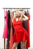 Blondes Mädchen in einem roten Kleid Front des Kleiderbügels Lizenzfreie Stockfotos