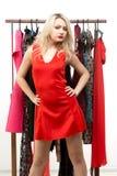 Blondes Mädchen in einem roten Kleid Front des Kleiderbügels Stockbild