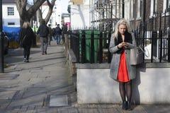 Blondes Mädchen in einem roten Kleid liest die Nachrichten am Telefon und lehnt sich Stockbild
