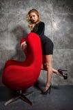 Blondes Mädchen in einem schwarzen Kleid, das nahe rotem Lehnsessel steht Stockfotografie