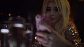 Blondes Mädchen in einem trinkenden Champagner des Vereins mit Freunden und dem Nehmen eines selfie stock video