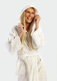 Blondes Mädchen in einem weißen Bademantellächeln Stockfotografie