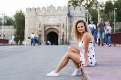 Blondes Mädchen in einem weißen Kleid, das auf einem Bürgersteig auf der Brücke sitzt Lizenzfreies Stockfoto