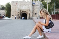 Blondes Mädchen in einem weißen Kleid, das auf einem Bürgersteig auf der Brücke sitzt Stockbild
