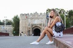 Blondes Mädchen in einem weißen Kleid, das auf einem Bürgersteig auf der Brücke sitzt Lizenzfreie Stockfotos