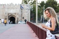 Blondes Mädchen in einem weißen Kleid, das auf der Brücke steht und a verwendet Stockbild