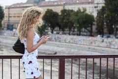 Blondes Mädchen in einem weißen Kleid, das auf der Brücke steht und a verwendet Stockbilder