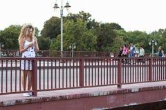 Blondes Mädchen in einem weißen Kleid, das auf der Brücke steht und a verwendet Stockfotografie
