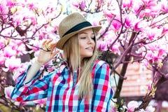 Blondes Mädchen genießen das Leben mit Blumen von hinten Lizenzfreies Stockbild