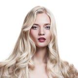 Blondes Mädchen. Gesundes langes lockiges Haar. Stockbild