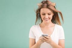 Blondes Mädchen hält Telefon Stockfoto