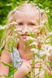Blondes Mädchen, ihr sommersprossiges Gesicht, sitzend im grünen Gras mit Stockfoto
