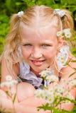 Blondes Mädchen, ihr sommersprossiges Gesicht, sitzend im grünen Gras mit Lizenzfreie Stockbilder