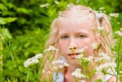 Blondes Mädchen ihr sommersprossiges Gesicht, sitzend im grünen Gras mit f Lizenzfreie Stockfotos