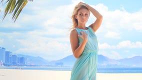 blondes Mädchen im Azurblau berührt Haarfehlschlag unter Wind auf Strand stock video