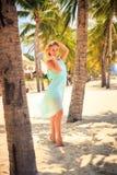 blondes Mädchen im Azurblau gehen an mit der Hand auf Kopf unter Palmen auf den Zehen Lizenzfreie Stockbilder