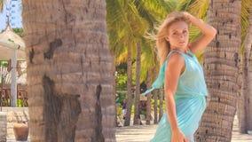 blondes Mädchen im Azurblau hebt Hände hinter Kopf unter Palmen an stock footage