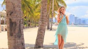 blondes Mädchen im Azurblau hebt Handwege unter Palmen auf Strand an stock footage