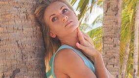 Blondes Mädchen im Azurblau lehnt sich auf Palmenstamm glatt macht Fehlschlag stock footage