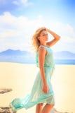 blondes Mädchen im Azurblau untersucht Abstand auf Strand Stockfotos