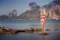Blondes Mädchen im Badeanzugstand auf Seesteinen Stockbilder