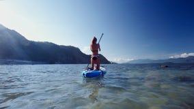Blondes Mädchen im Bikini überschreitet vorbei auf paddleboard Rückseitenansicht stock footage