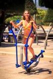 Blondes Mädchen im Bikini bildet auf Stepper im Park nahe Strand aus Lizenzfreie Stockfotografie