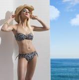 Blondes Mädchen im Bikini nahe der Wand mit Hut Lizenzfreie Stockfotos