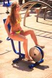 Blondes Mädchen im Bikini sitzt auf Fahrradsimulatorlächeln im Freien Stockfoto