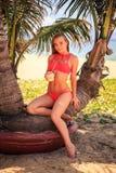 blondes Mädchen im Bikini sitzt auf Palme hält Kokosnuss verbogenes Knie Stockfotografie