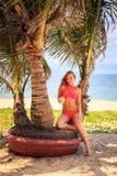 blondes Mädchen im Bikini sitzt auf Palme hält Kokosnussblicke nahe Meer Lizenzfreies Stockbild