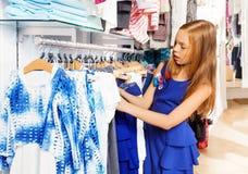 Blondes Mädchen im blauen Kleid, das Kleidung am Speicher wählt Stockfotografie