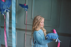 Blondes Mädchen im blauen Kleid mit Vögeln Stockbild