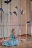 Blondes Mädchen im blauen Kleid mit Vögeln Stockbilder