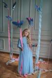 Blondes Mädchen im blauen Kleid mit Vögeln Stockfotografie