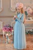Blondes Mädchen im blauen Kleid und mit einer Blume auf dem Kopf Stockfotografie