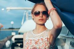 Blondes Mädchen im Blumenkleid und -Sonnenbrille, die Boot halten, segelt Lizenzfreies Stockfoto