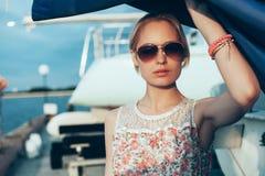 Blondes Mädchen im Blumenkleid und -Sonnenbrille, die Boot halten, segelt Stockfotos