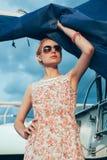 Blondes Mädchen im Blumenkleid und -Sonnenbrille, die Boot halten, segelt Lizenzfreie Stockfotos