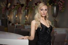 Blondes Mädchen im Café im schwarzen Kleid Stockfotografie