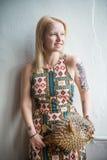 Blondes Mädchen im ethnischen Kleid mit einem Fischpuffer Lizenzfreie Stockfotografie