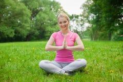Blondes Mädchen im Freien im Park, der rosa T-Shirt trägt yoga Stockbilder