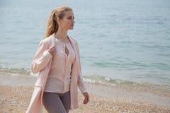 Blondes Mädchen im Herbst geht auf den Strand-Ozean lizenzfreie stockfotos
