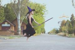 Blondes Mädchen im Hexenkostüm fliegt auf Besenstiel Stockfoto